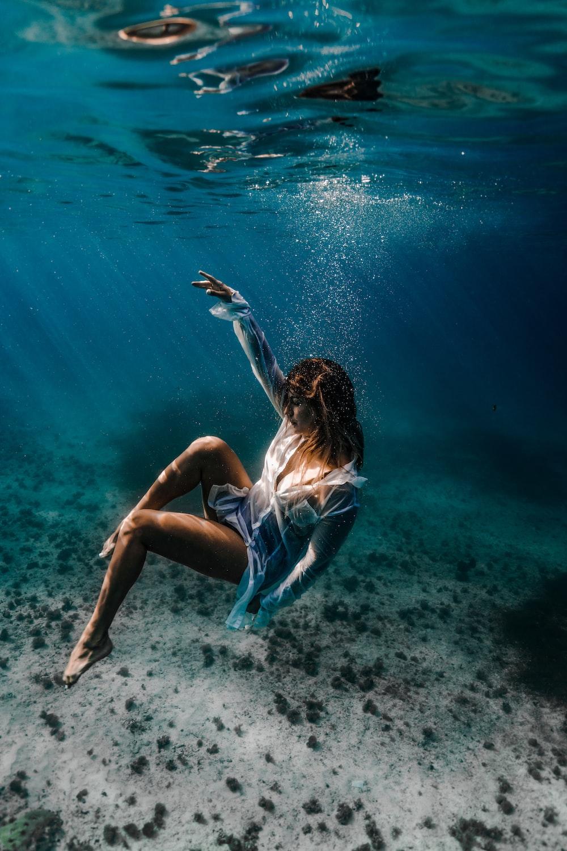 woman in blue and white bikini lying on water