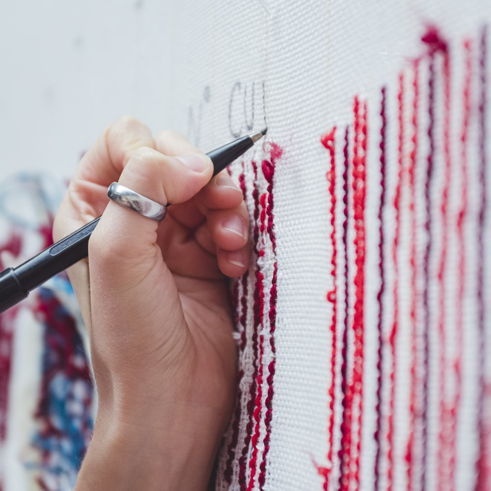person holding black pen and red and white textile