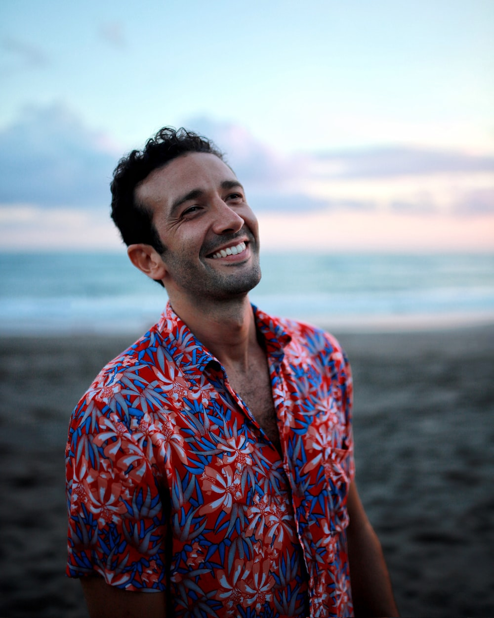 man in blue and orange button up shirt smiling
