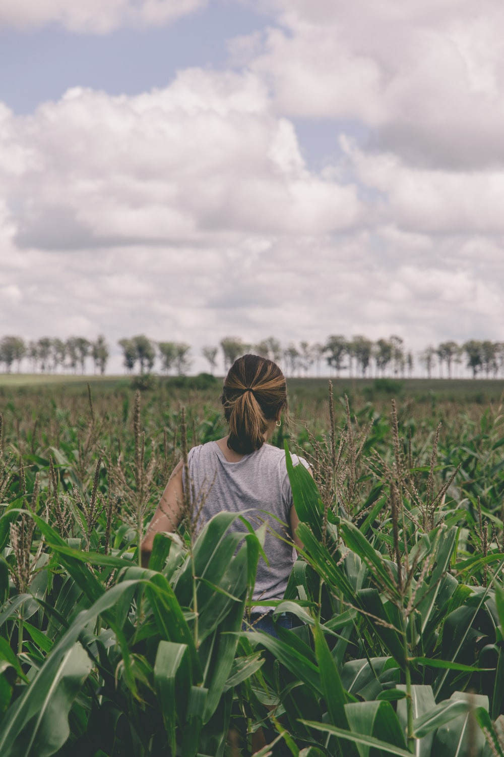 woman in gray shirt standing on green grass field during daytime
