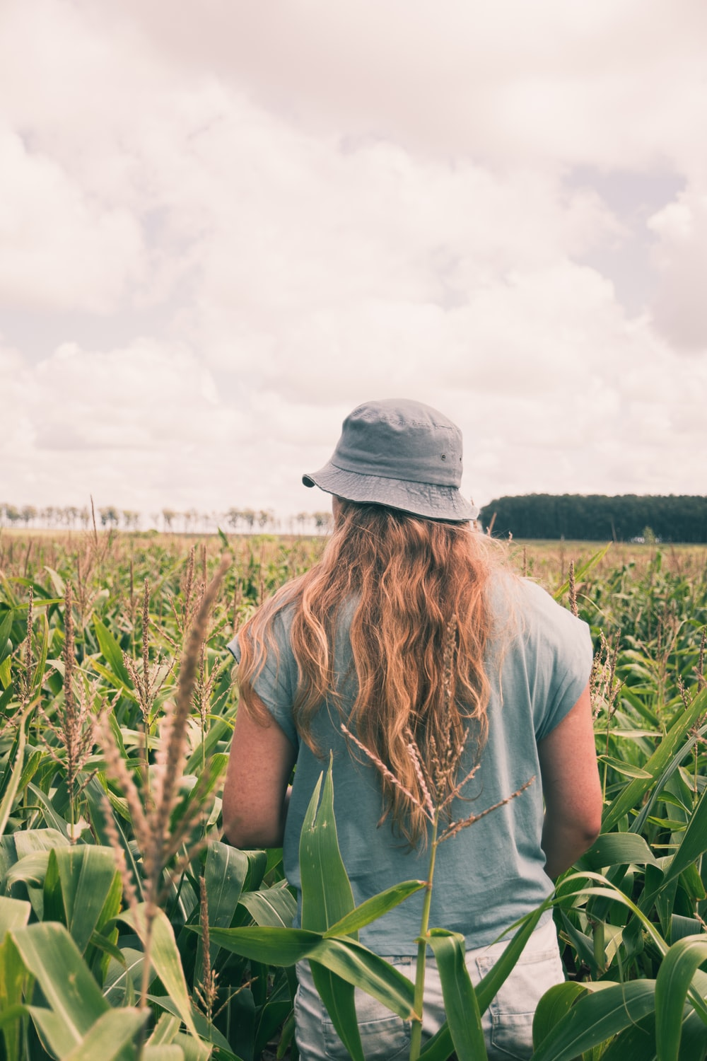 woman in grey hat standing on green grass field during daytime