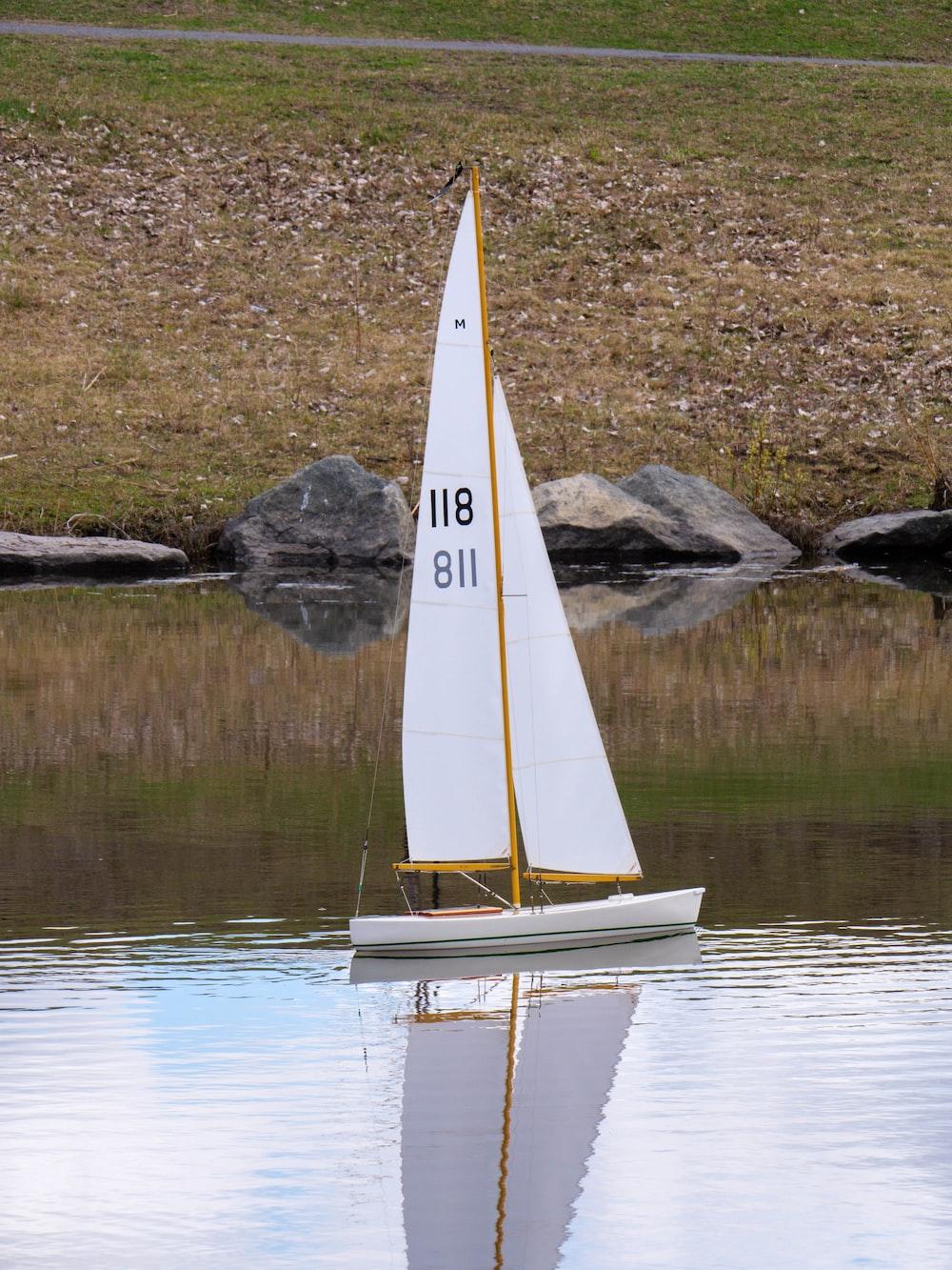 white sail boat on lake during daytime