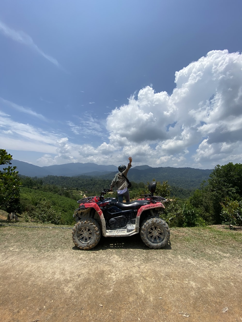 woman in red and black atv on dirt road during daytime