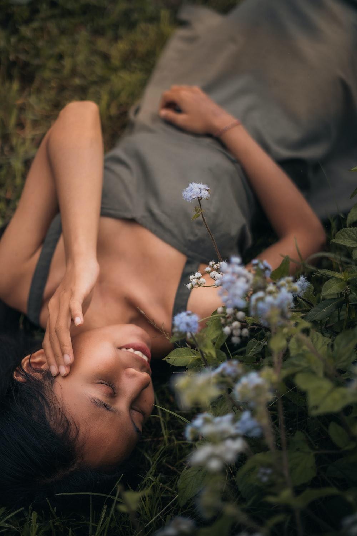 woman in gray shirt lying on green grass field