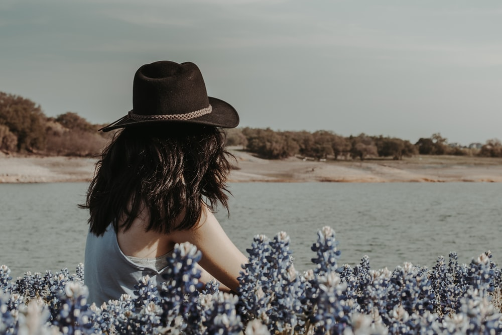 woman in blue and white floral shirt wearing brown hat standing on brown sand near body