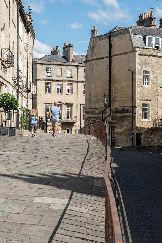 people walking on sidewalk near brown concrete building during daytime