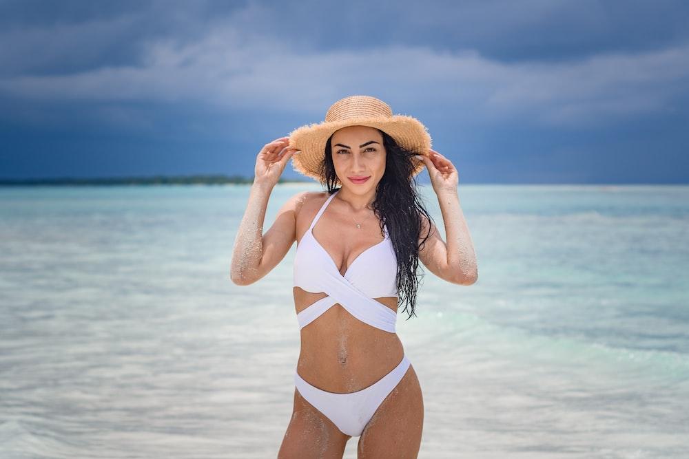 woman in white bikini wearing brown sun hat standing on beach during daytime