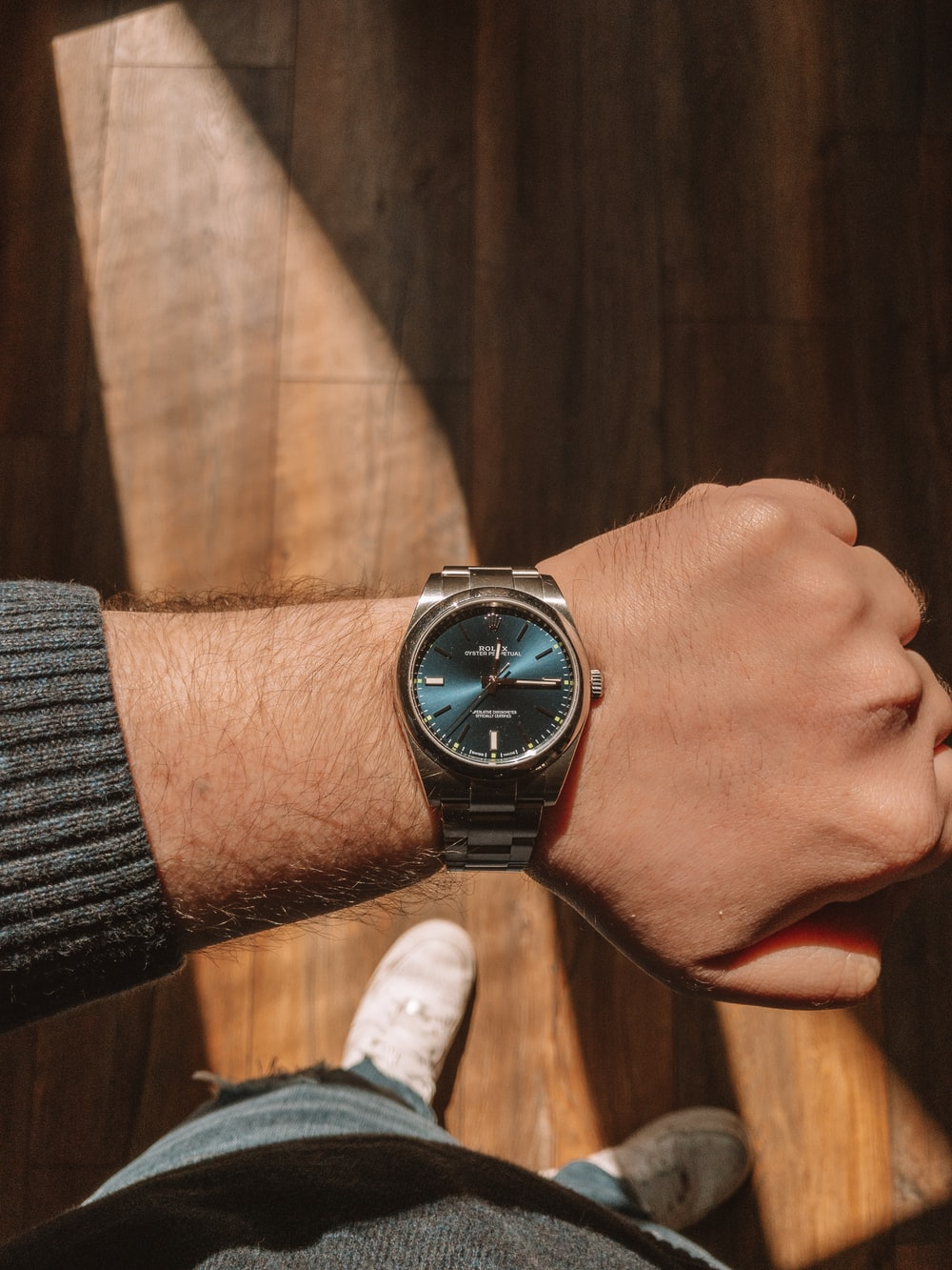 person wearing silver round analog watch