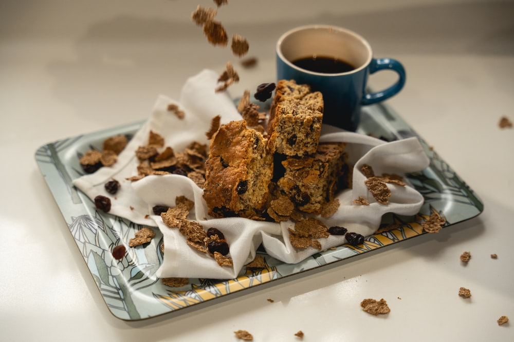 brown cookies on white ceramic plate beside blue ceramic mug
