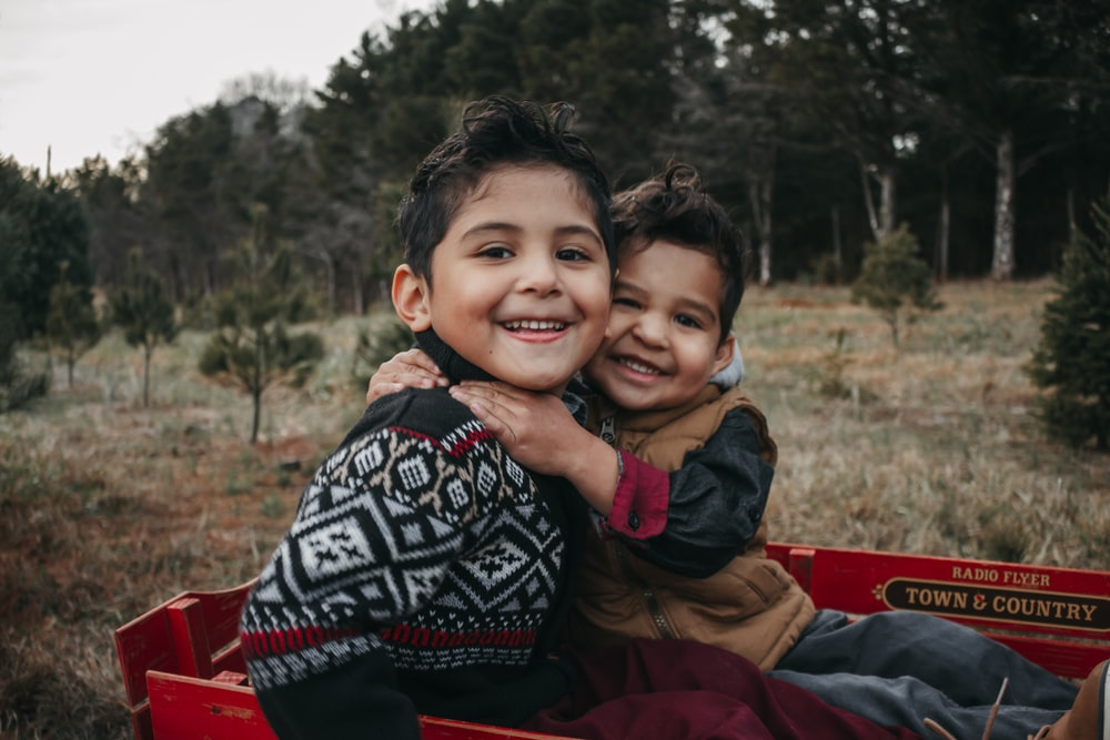 boy in black and white tribal print jacket smiling beside boy in red jacket