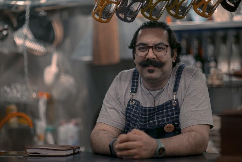 man in gray and blue crew neck shirt wearing black framed eyeglasses