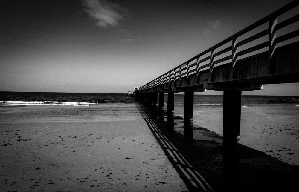 grayscale photo of wooden dock on beach