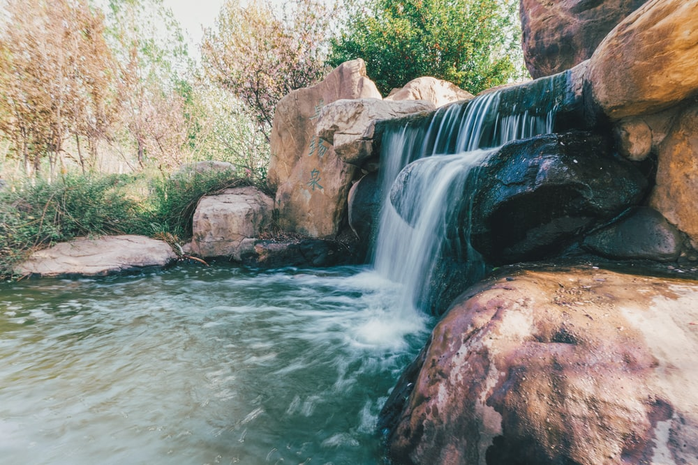 water falls between brown rocks and green trees during daytime