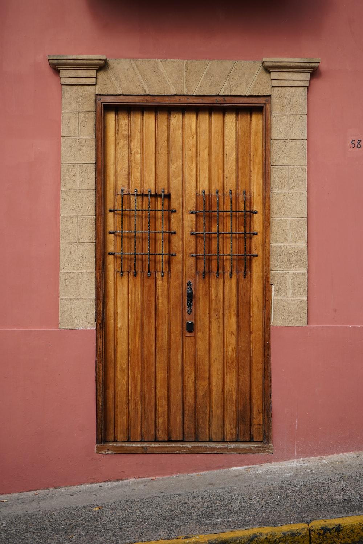 brown wooden door on pink concrete wall