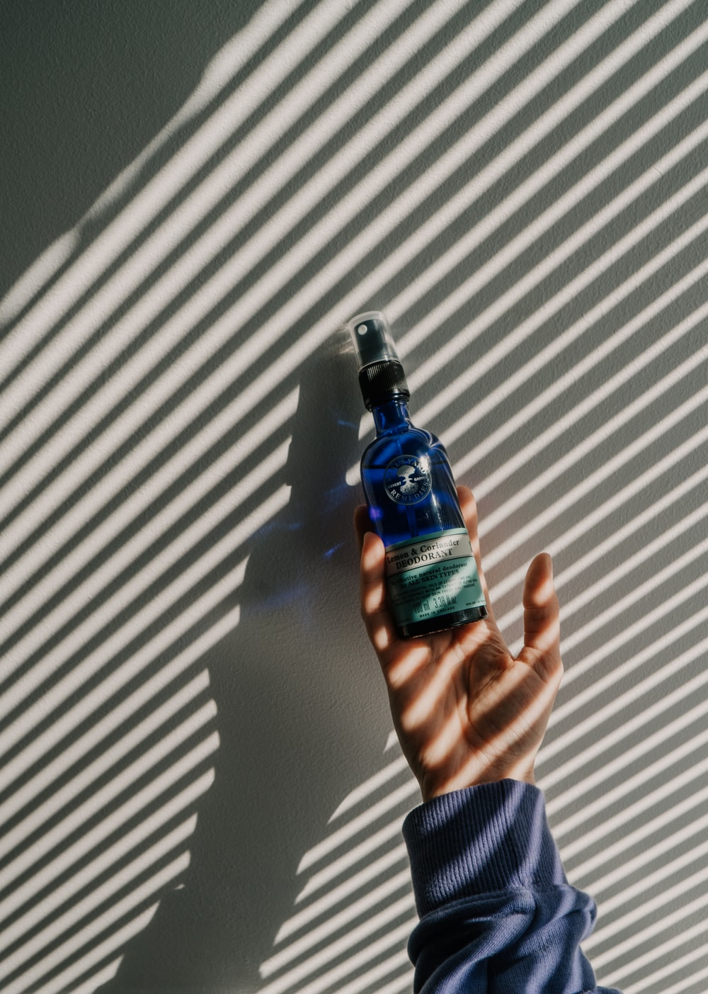 person holding blue and black bottle