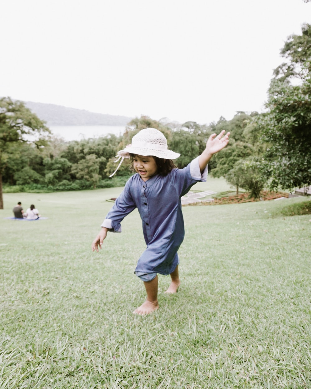 boy in blue t-shirt and blue shorts walking on green grass field during daytime