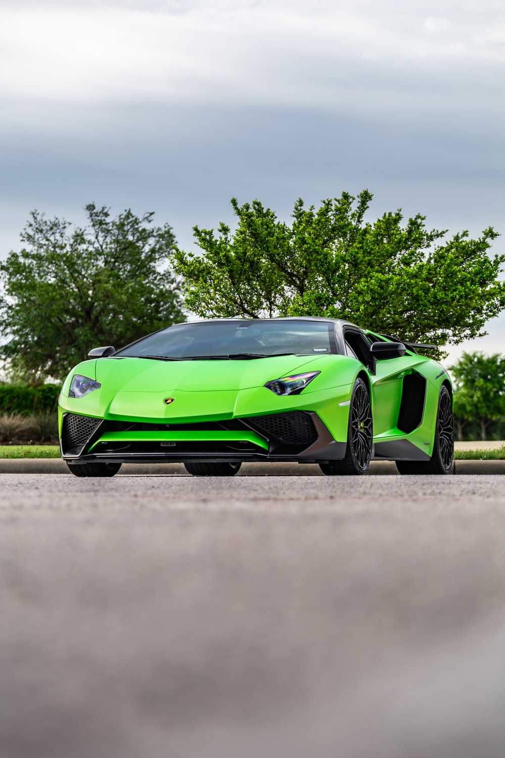 green and black lamborghini aventador parked on brown field during daytime