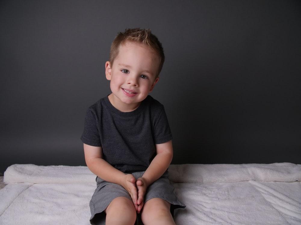 boy in black crew neck t-shirt sitting on white bed