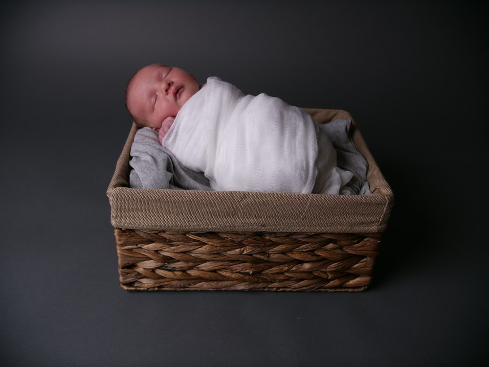 baby in white blanket in brown woven basket