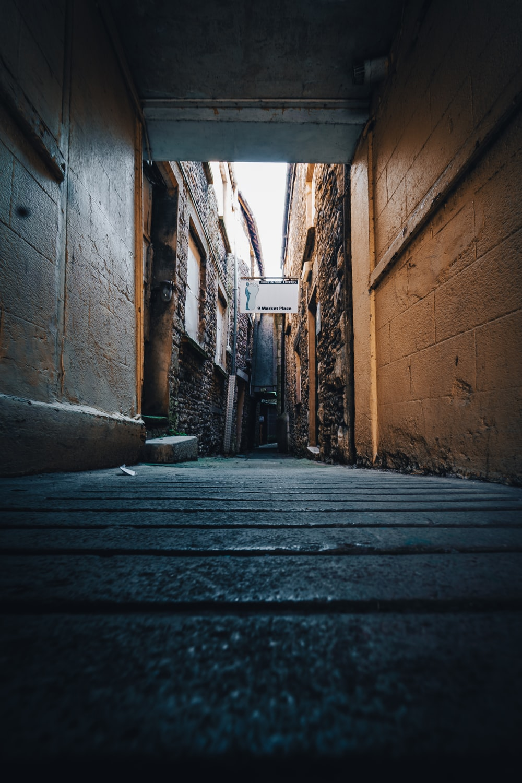 brown wooden pathway between brown brick wall