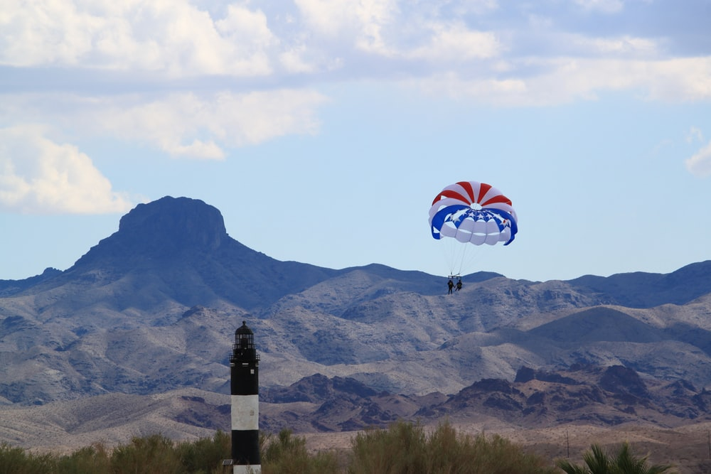 person in red white and blue parachute over mountain during daytime