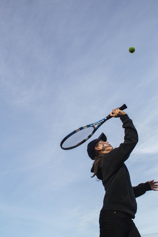 man in black jacket holding tennis racket