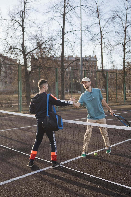 2 men playing tennis on court during daytime