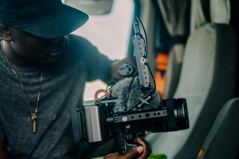 man in black hoodie holding black video camera