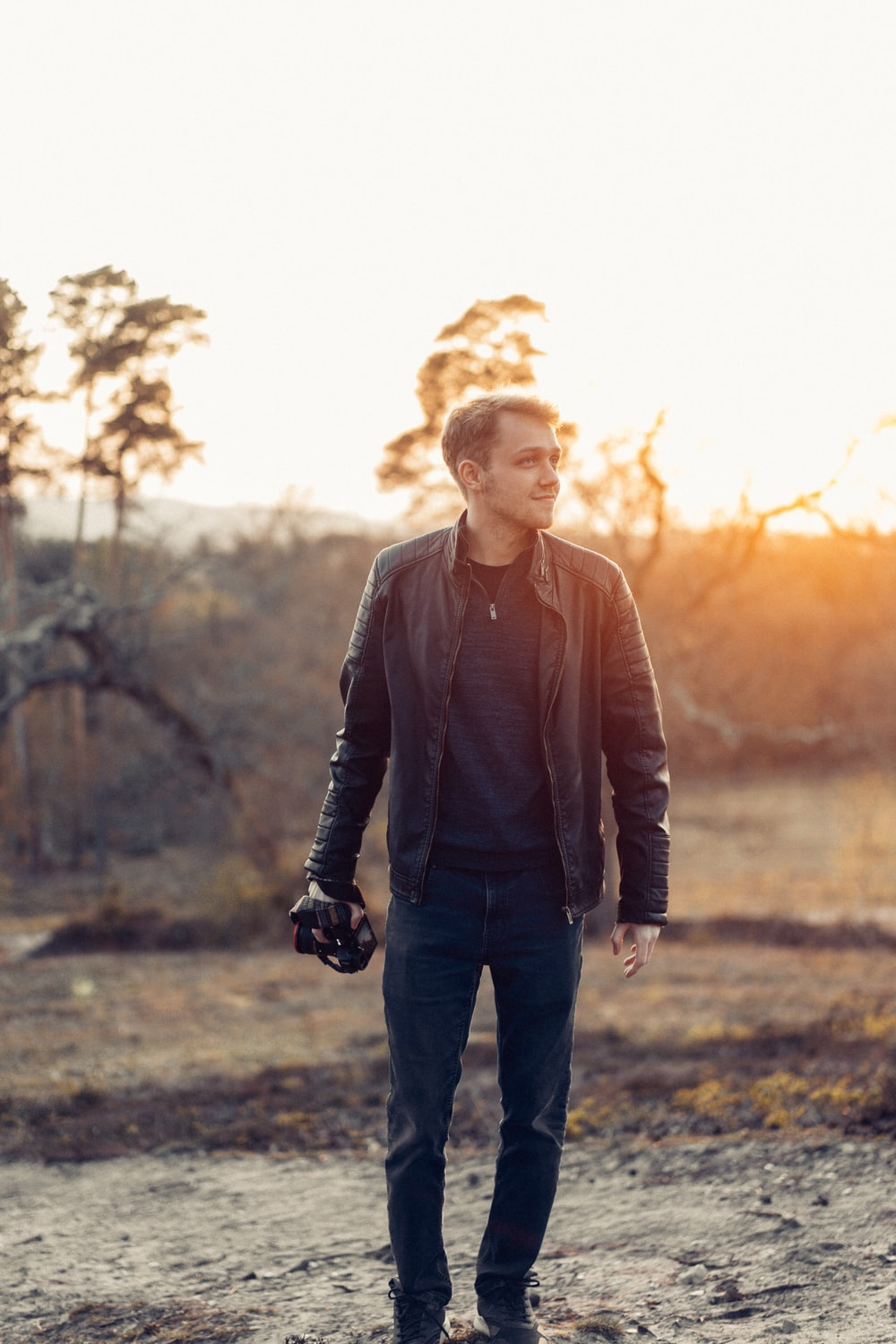 man in black leather jacket standing on grass field during daytime