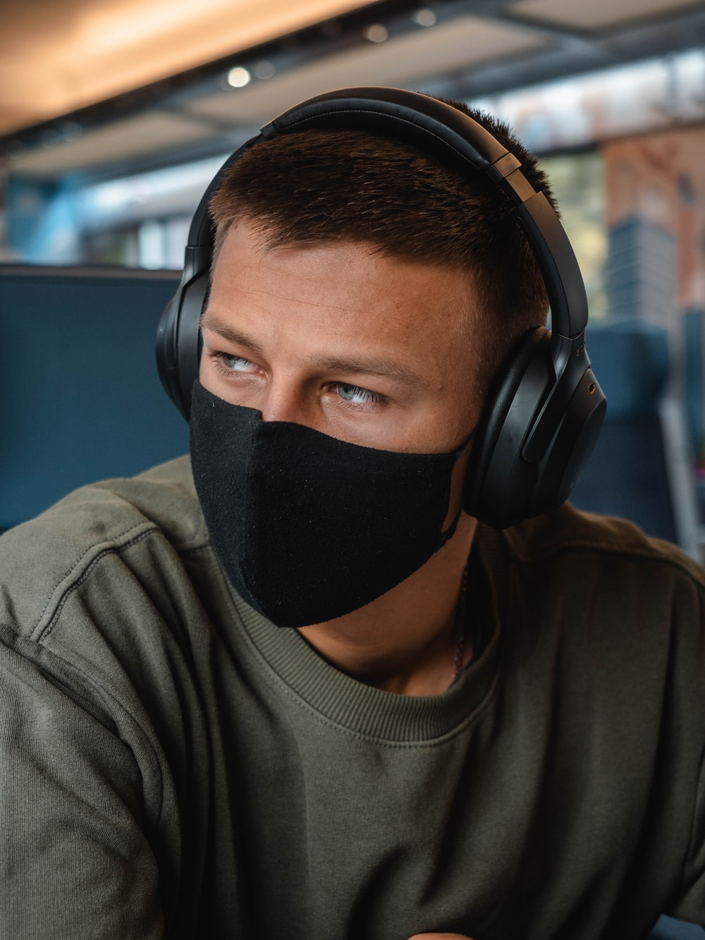 man in grey crew neck shirt wearing black headphones