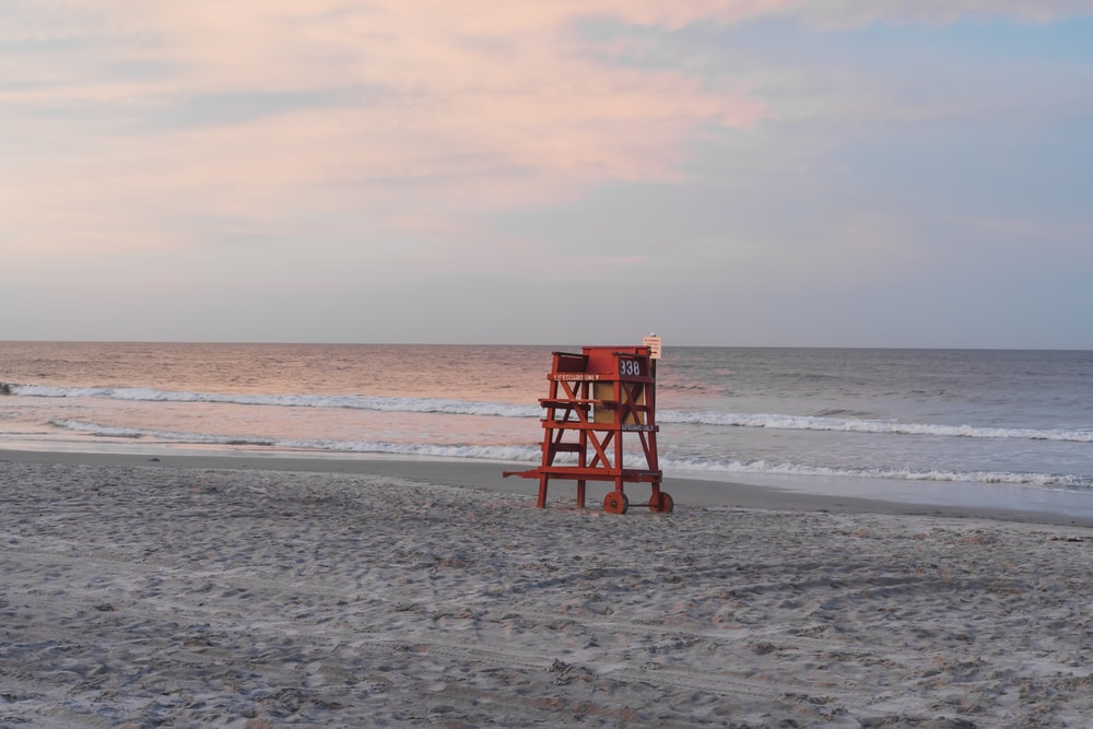 red wooden lifeguard chair on beach during daytime
