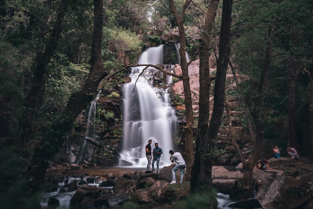 people standing on rock near waterfalls during daytime