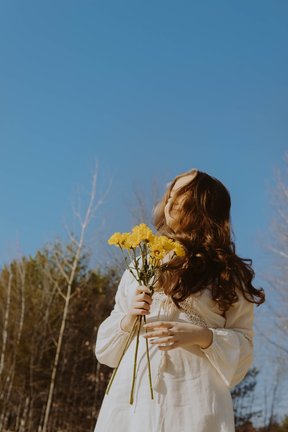 woman in white long sleeve shirt holding yellow flower during daytime