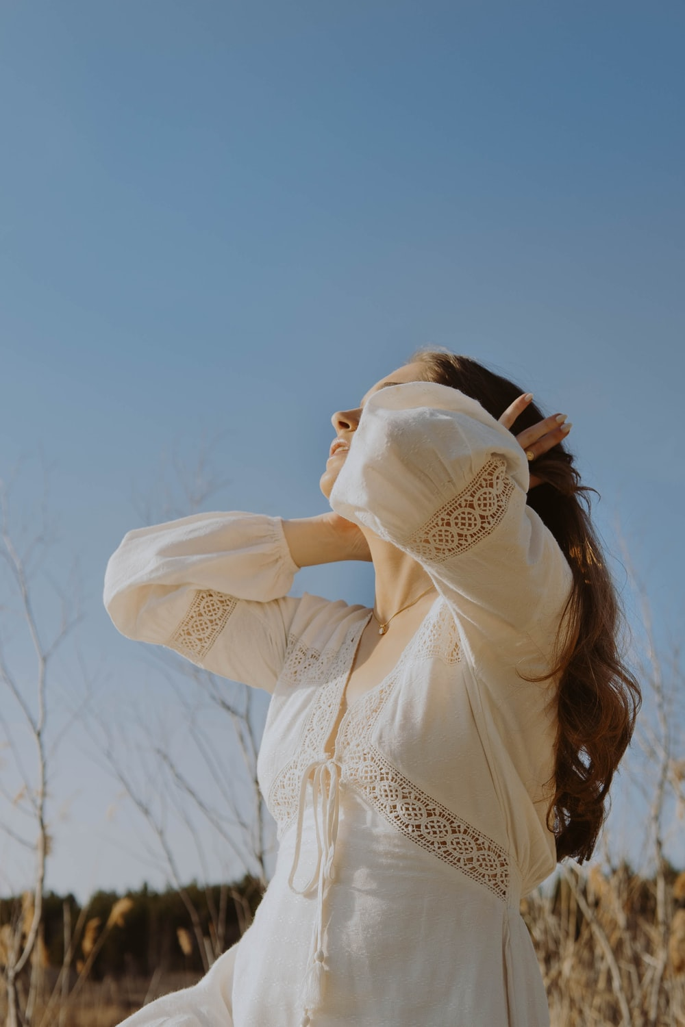 woman in white long sleeve shirt covering her face with white scarf