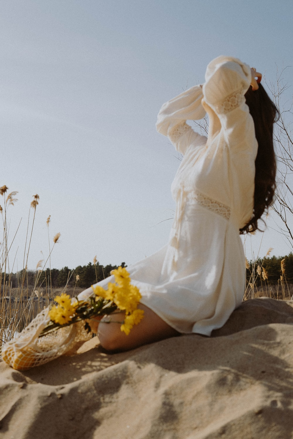 woman in white dress sitting on brown sand during daytime