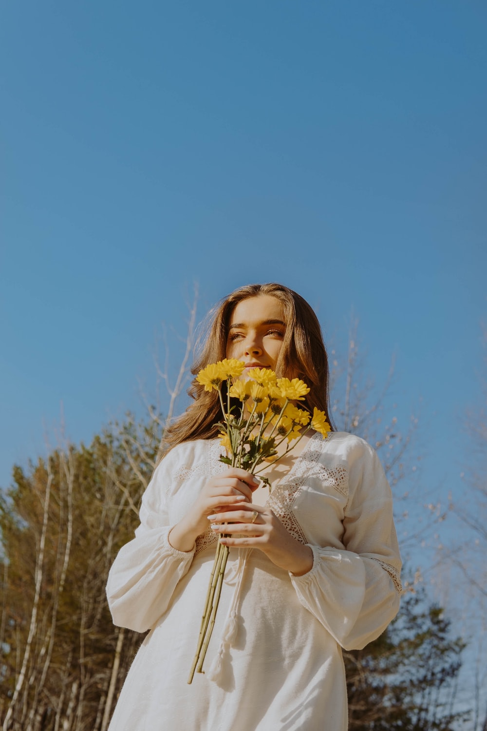 woman in white long sleeve shirt holding yellow flowers