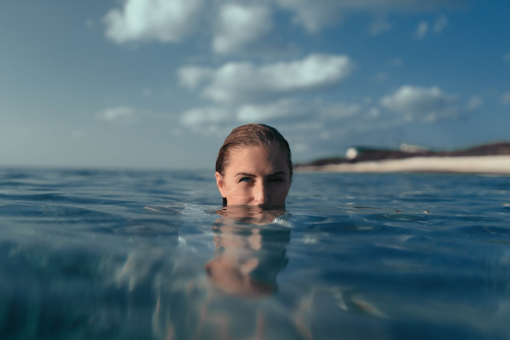 boy in water under blue sky during daytime