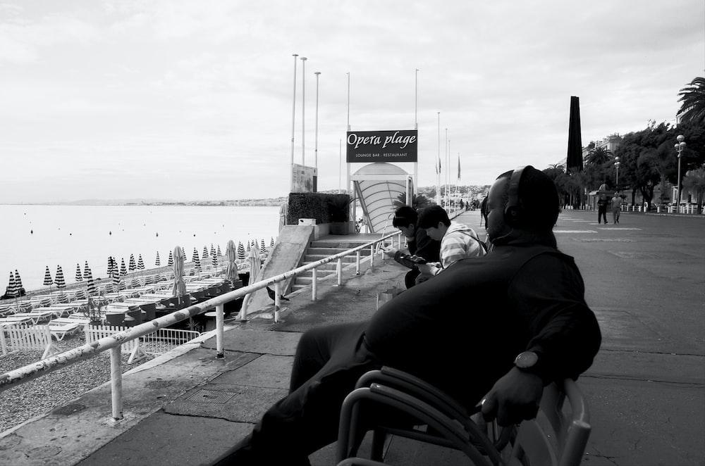 grayscale photo of people walking on the bridge