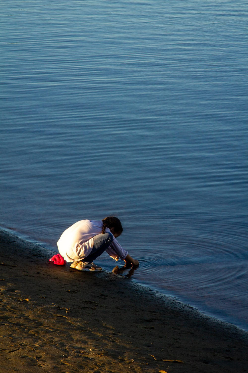 child in white shirt and brown shorts sitting on water during daytime