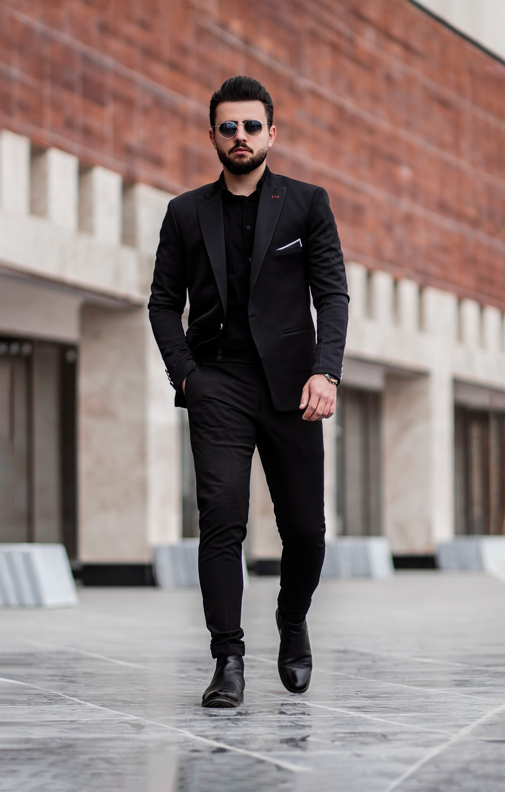 man in black suit jacket and black pants standing on gray concrete floor during daytime