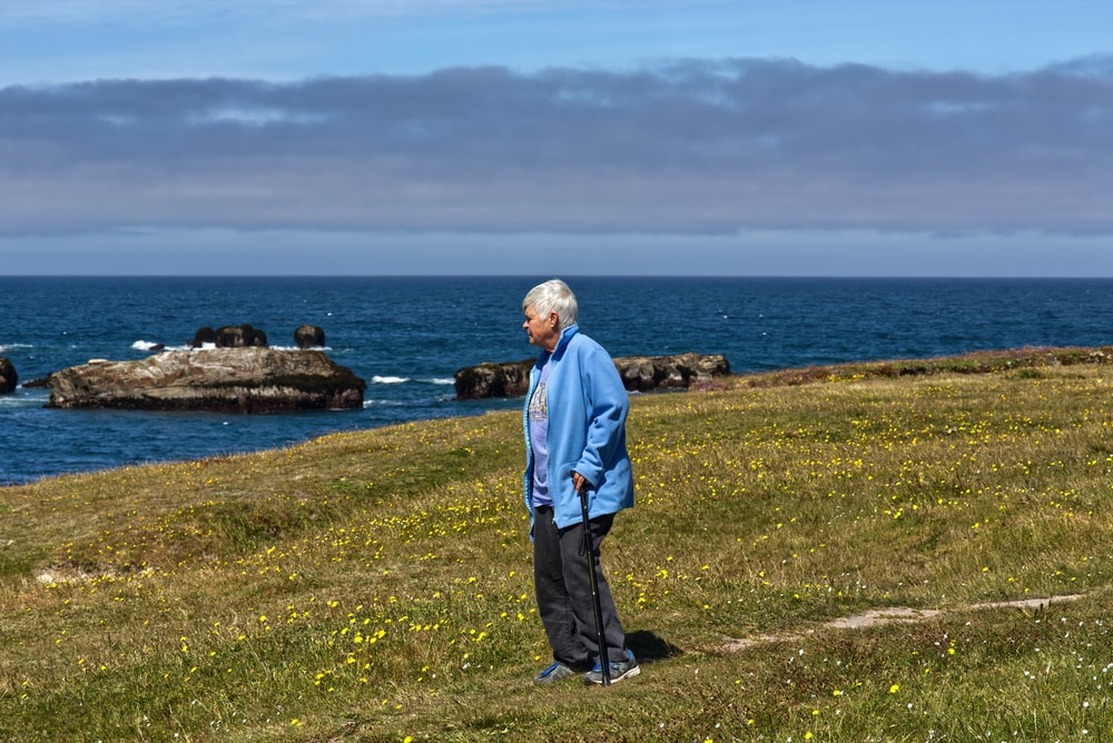 man in blue jacket standing on green grass field near body of water during daytime