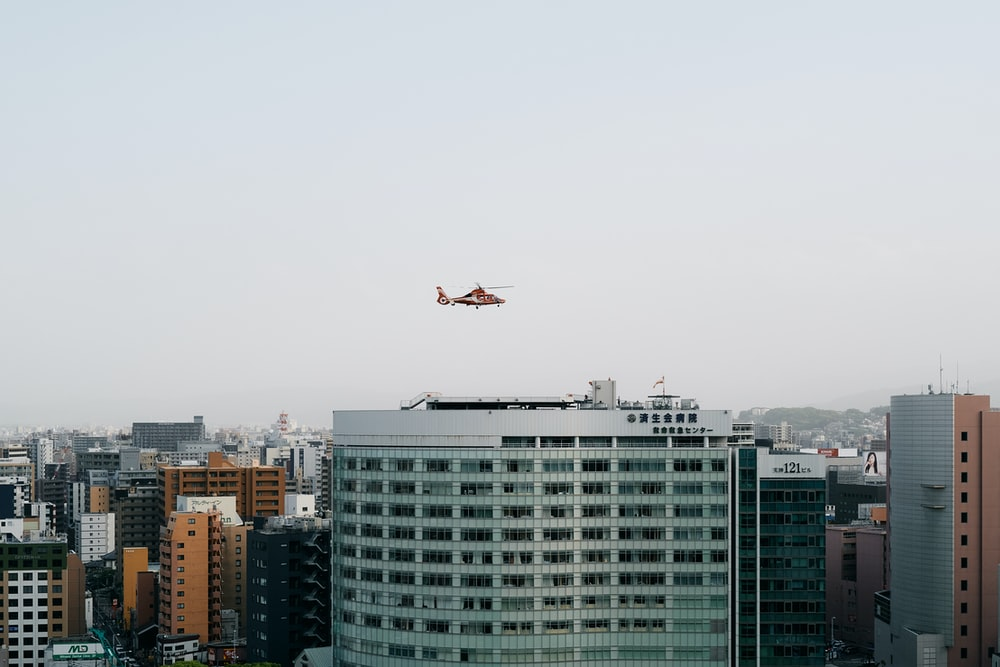 white airplane flying over city buildings during daytime