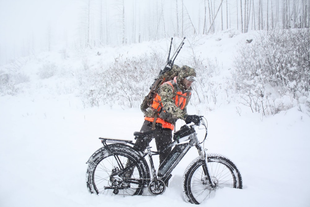 woman in black jacket riding on black mountain bike on snow covered ground during daytime
