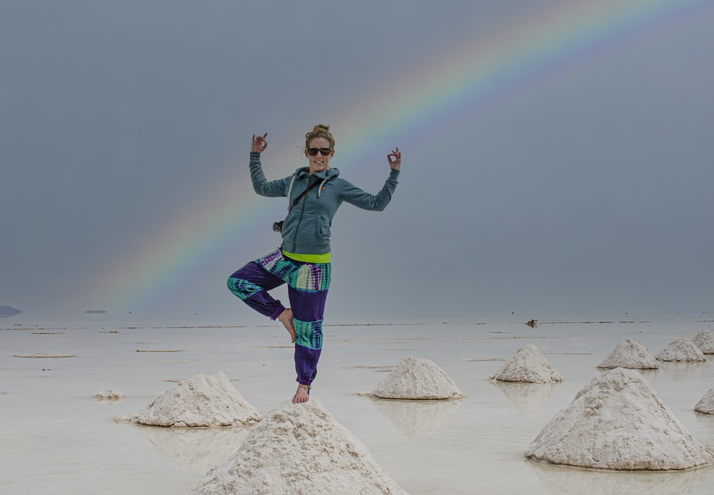 girl in green jacket and blue pants standing on white sand during daytime
