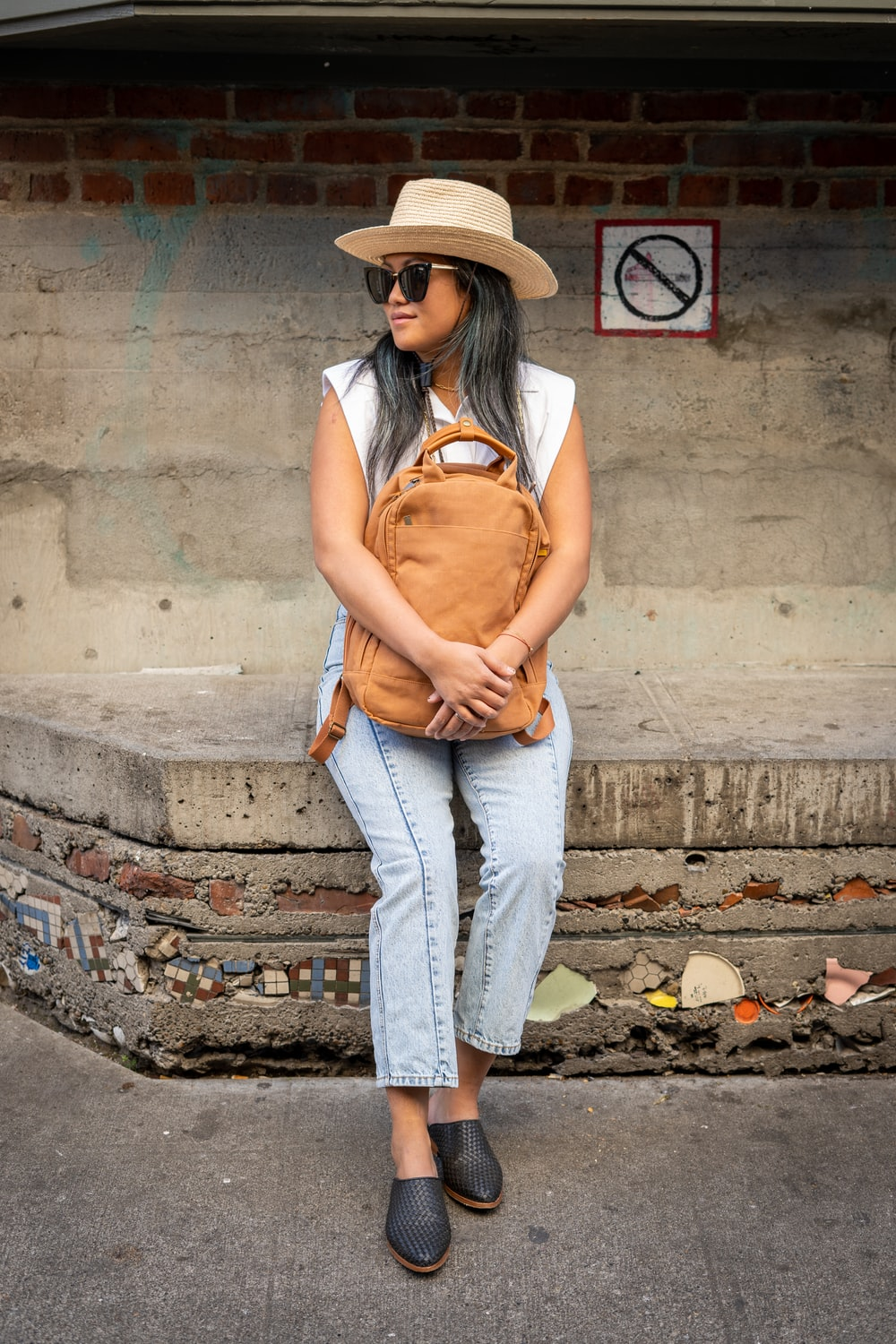 woman in brown tank top and blue denim jeans wearing brown hat standing on gray concrete