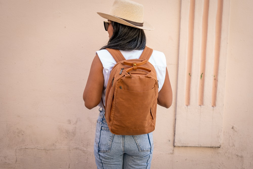 woman in white shirt and blue denim jeans with brown backpack