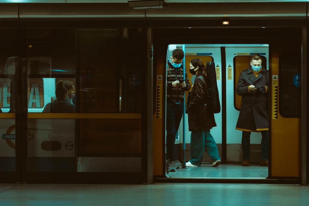 man in black coat standing in front of glass door