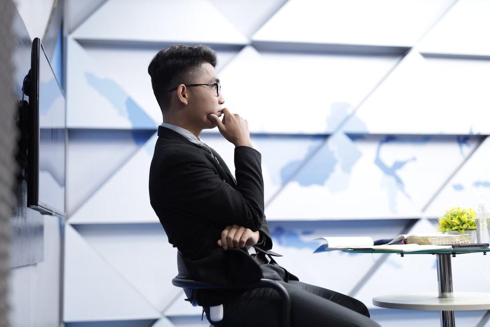 man in black long sleeve shirt sitting on black chair