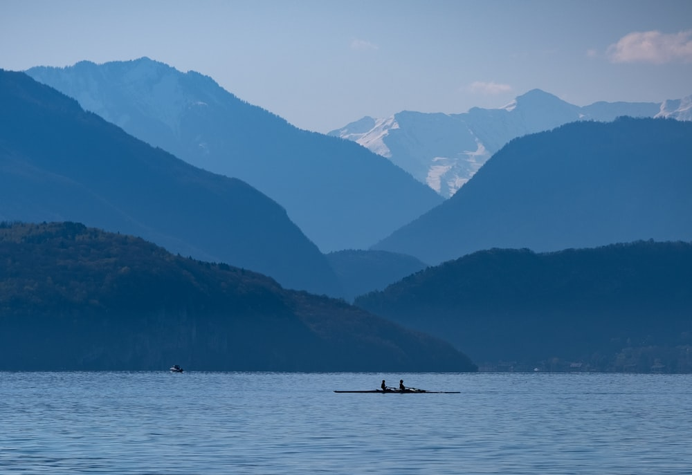 silhouette of 2 people riding boat on lake during daytime