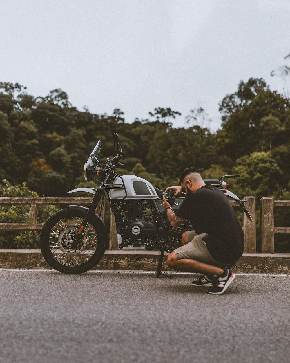 man in black jacket riding black cruiser motorcycle